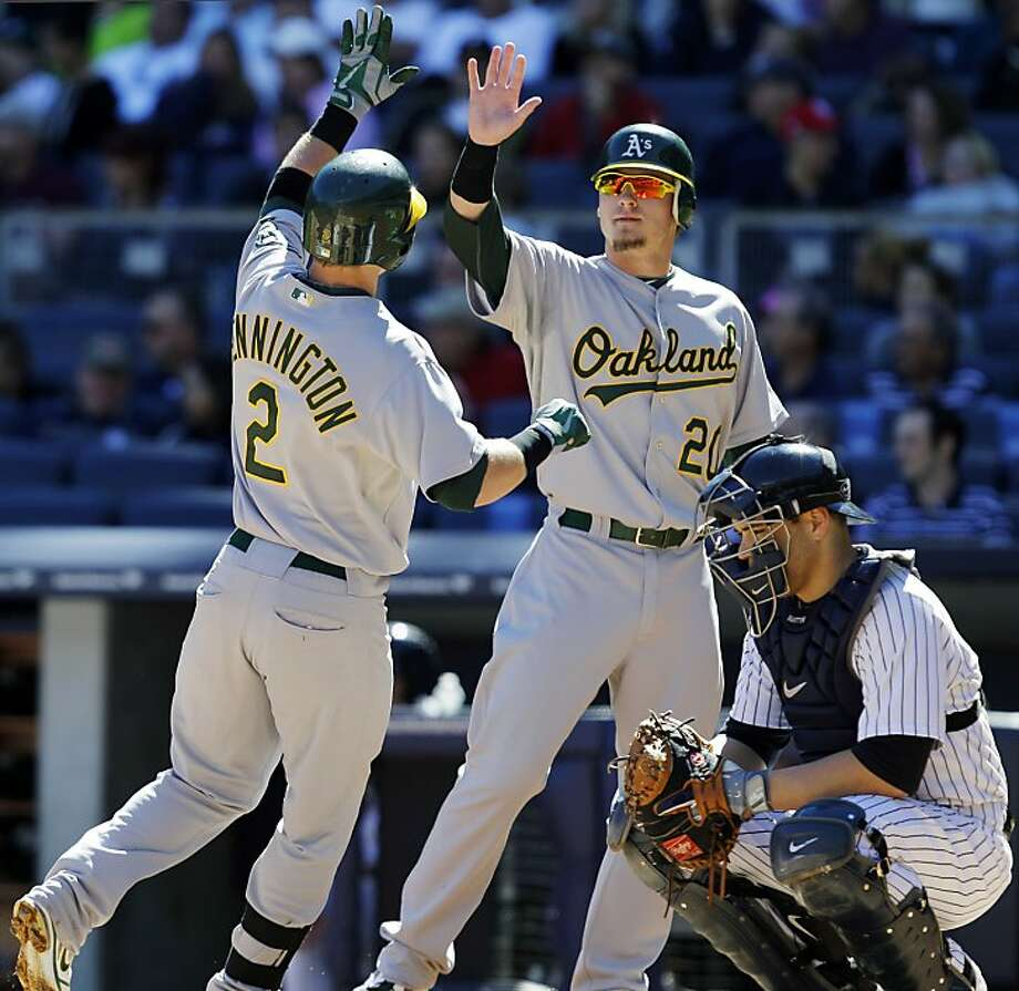 Oakland Athletics' Josh Donaldson congratulates Cliff Pennington at the plate after Pennington's second-inning, two-run home run off New York Yankees starting pitcher Hiroki Kuroda in their baseball game at Yankee Stadium in New York, Sunday, Sept. 23, 2012. Yankees catcher Russell Martin crouches at bottom left. (AP Photo/Kathy Willens) Photo: Kathy Willens, Associated Press
