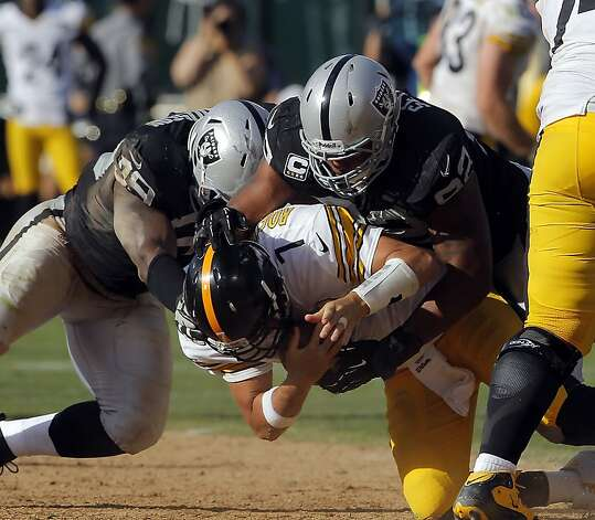 Richard Seymour, right, and Lamarr Houston, left, sack Ben Roethlisberger in the final minutes. The Oakland Raiders played the Pittsburgh Steelers at O.co Coliseum in Oakland, Calif., on Sunday, September 23, 2012, and defeated the Steelers 34-31. Photo: Carlos Avila Gonzalez - San Fran, The Chronicle