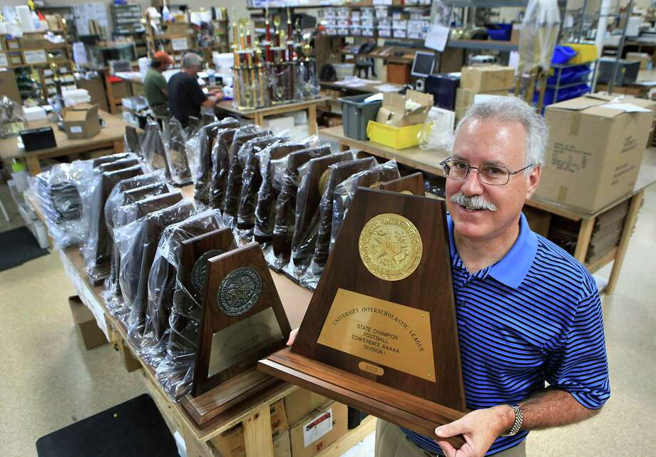 Charlie Drago, owner of Monarch Trophy Studio holds the UIL State Champion Football trophy in his workshop, where all the UIL trophies are made.  Thursday, Sept. 13, 2012. Photo: BOB OWEN, San Antonio Express-News / © 2012 San Antonio Express-News