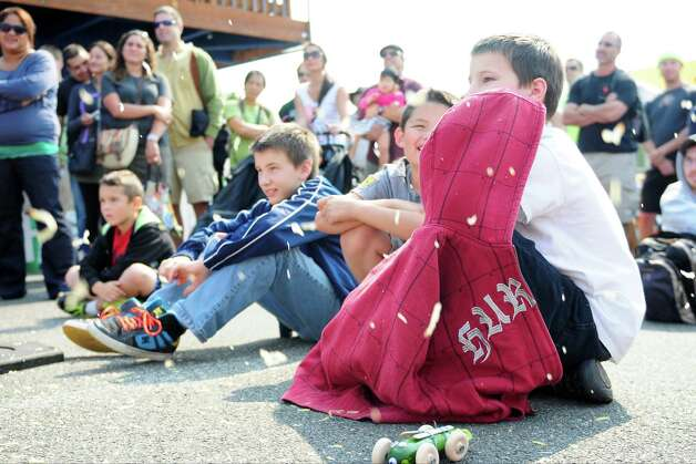"Children watch as the Texas Chainsaw Pumpkin Carving competition gets underway at Fremont's Oktoberfest on Sunday, Sept. 23, 2012. The competitors, all dressed in costume, worked on their ""art"" while sending sprays of pumpkin guts in all directions. Photo: LINDSEY WASSON / SEATTLEPI.COM"