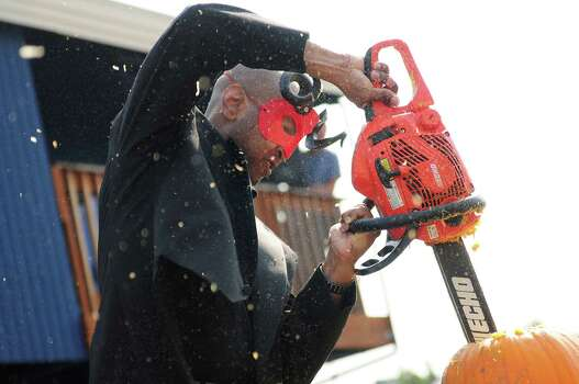 """""""The Devil"""" works on dislodging the top of his pumpkin. Photo: LINDSEY WASSON / SEATTLEPI.COM"""