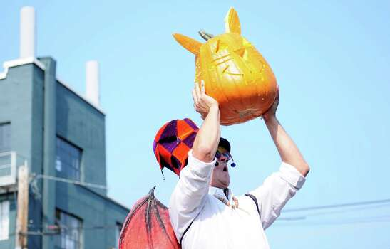 David Roman holds up a creation for the crowd's appraisal during the Texas Chainsaw Pumpkin Carving competition. Photo: LINDSEY WASSON / SEATTLEPI.COM