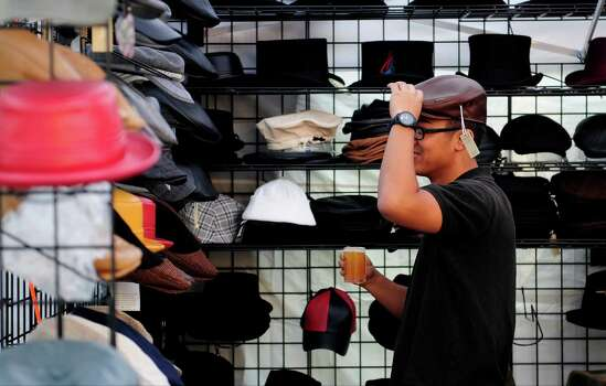 Arman Reyes of Arizona tries on a hat at a vendor's booth. Photo: LINDSEY WASSON / SEATTLEPI.COM