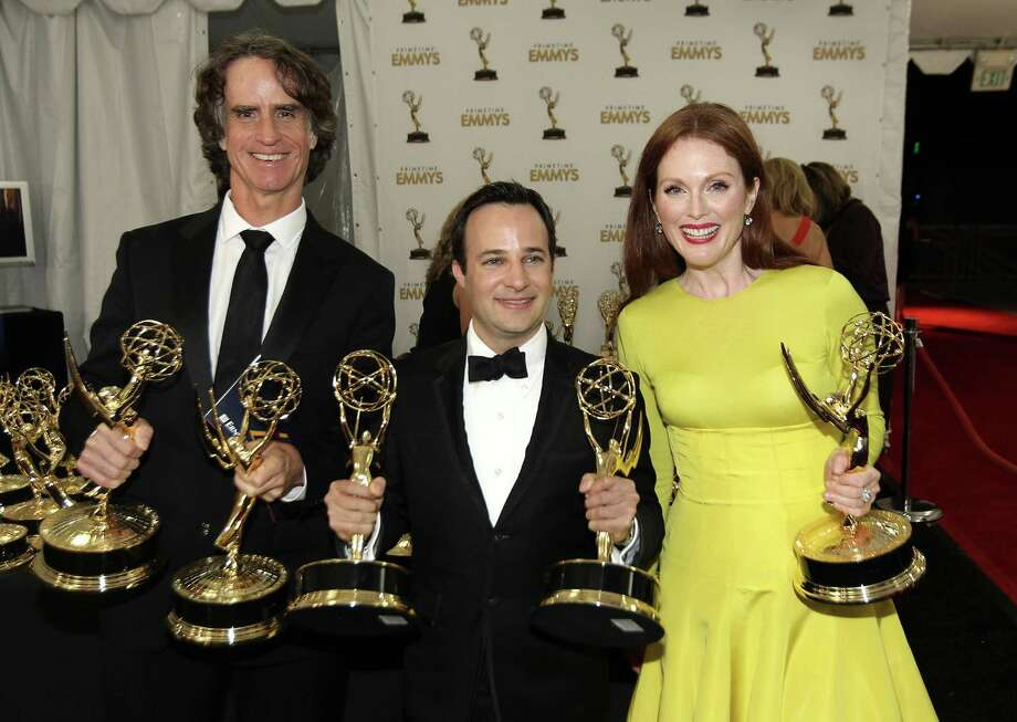 "From left, Director Jay Roach, writer Danny Strong, and Actress Julianne Moore, pose backstage with the awards they won for the HBO movie ""Game Change,"" at the 64th Primetime Emmy Awards at the Nokia Theatre on Sunday, Sept. 23, 2012, in Los Angeles. (Photo by Matt Sayles/Invision/AP) Photo: AP"