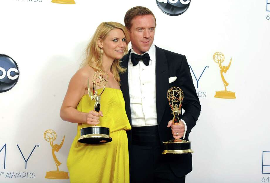 """Actress Claire Danes, winner of the Emmy for outstanding lead actress in a drama series for """"Homeland,"""" left, and actor Damien Lewis, winner of the Emmy for outstanding lead actor in a drama series for """"Homeland"""" pose together backstage at the 64th Primetime Emmy Awards at the Nokia Theatre on Sunday, Sept. 23, 2012, in Los Angeles. (Photo by Jordan Strauss/Invision/AP) Photo: Jordan Strauss"""