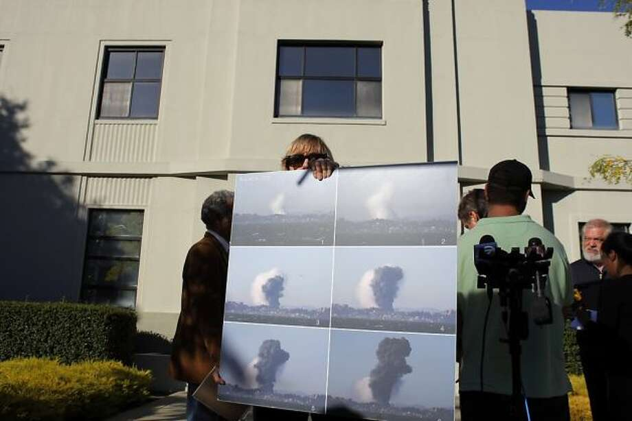 Shauna Lawhorne, with Chemical Safety Board public affairs, displays photos on Monday, August 20, 2012 in Richmond, Calif., of the vapor cloud at the Chevron refinery that exploded on Aug. 6. Photo: Carlos Avila Gonzalez, The Chronicle / SF