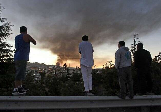 Above: Residents stand atop a guardrail to get a view of the fire. People in the area were repeatedly warned to stay inside to avoid breathing tainted air. Photo: Lance Iversen, The Chronicle / SF