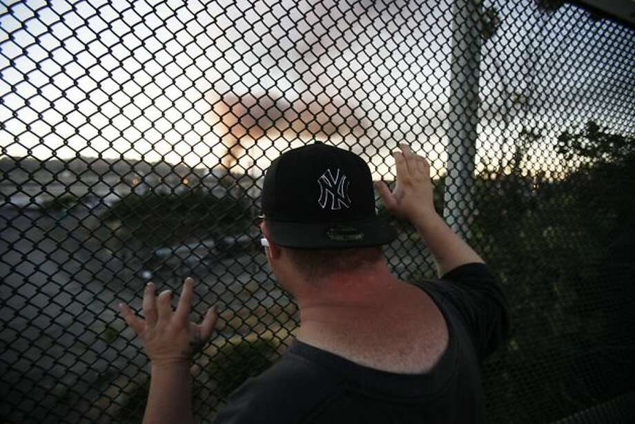 John Smith, of Richmond, watches the Chevron Oil Refinery fire from a distance through a fence on Castro Road in Richmond, Calif. on Monday, Aug. 6, 2012. Photo: Stephen Lam, Special To The Chronicle / SF