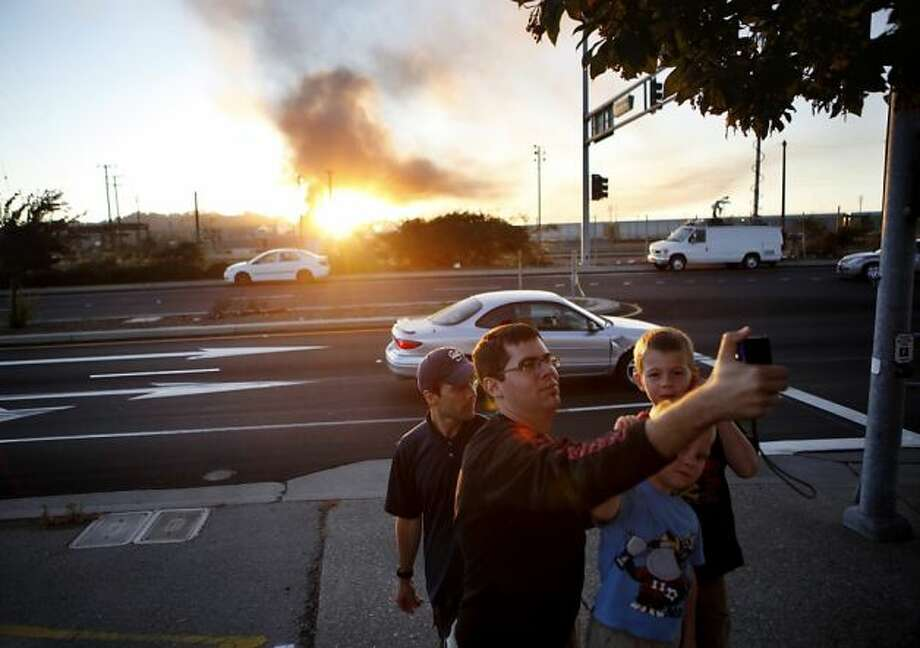 Andres Locky takes a photo of himself in front of plumes of smoke emanating from the Chevron oil refinery on Monday, August 6, 2012 in Richmond, Calif. Photo: Beck Diefenbach, Special To The Chronicle / SF