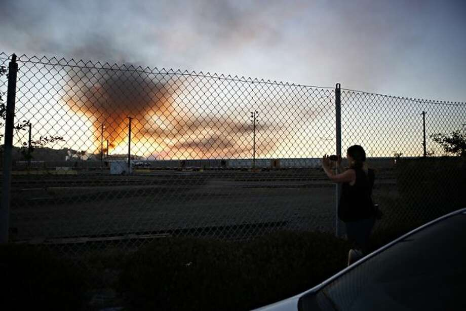 Elizabeth Fein, of El Cerrito, takes a photo of plumes of smoke emanating from the Chevron oil refinery on Monday, August 6, 2012 in Richmond, Calif. Photo: Beck Diefenbach, Special To The Chronicle / SF