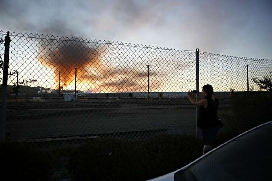 Elizabeth Fein, of El Cerrito, takes a photo of plumes of smoke emanating from the Chevron oil refin