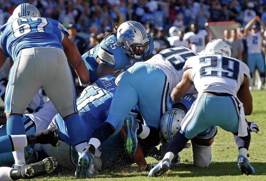 Tennessee Titans defenders Jurrell Casey (99) and Ryan Mouton (29) stop Detroit Lions quarterback Shaun Hill, lower right, from getting a first down on the final play in overtime to seal the Titans' 44-41 win in an NFL football game on Sunday, Sept. 23, 2012, in Nashville, Tenn. The defensive stand by the Titans stopped the Lions' drive and ended the game. (AP Photo/Wade Payne) Photo: Wade Payne