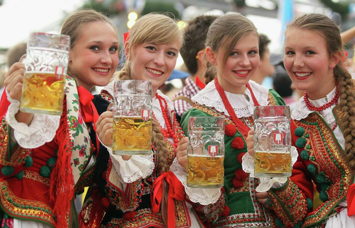 MUNICH, GERMANY - SEPTEMBER 23: Polish girls, dressed with traditional Polish costume enjoy drinking beer after participating in the opening parade during day 2 of Oktoberfest beer festival on September 22, 2012 in Munich, Germany.This year's edition of the world's biggest beer festival Oktoberfest will run until October 7, 2012.