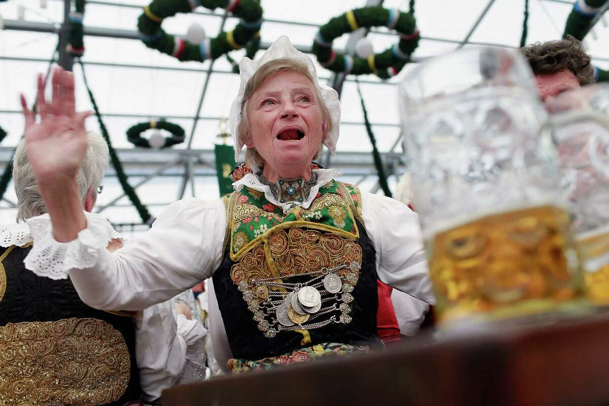 MUNICH, GERMANY - SEPTEMBER 23: A woman from Lower Bavaria, dressed with traditional ceremonial Bavarian costume enjoy drinking beer after participating in the opening parade during day 2 of Oktoberfest beer festival on September 22, 2012 in Munich, Germany.This year's edition of the world's biggest beer festival Oktoberfest will run until October 7, 2012.