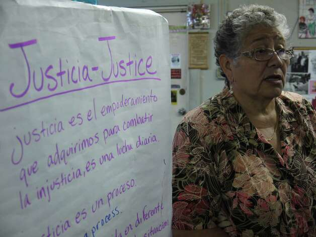 Petra Mata, co-founder of the sewing cooperative Fuerza Unida, in her office next to a sign about the group's continuing fight for justice. Photo: San Antonio Express-News
