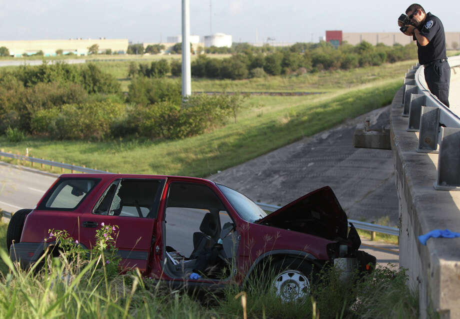 A police traffic investigator works at a scene where a SUV was left angled down the side of of a hill after it went veering off an access road, onto an exit ramp and crashing into a bridge along Loop 410. Officials at the crash site said the driver was traveling south along a Loop 410 frontage road near W.W. White Road about 7:30 a.m. when he suddenly lost control and went careening across a grassy area and into the highway's exit ramp for W.W. White. The vehicle then went off the exit ramp and onto an embankment and struck the bridge at W.W. White. The driver was pinned inside the SUV, which was left angled on its side down the steep hill. Using special equipment, officials rescued the man. The process took longer than usual because of the SUV's precarious position, officials said.   The man was taken to San Antonio Military Medical Center, but his condition was not immediately known. Photo: JOHN DAVENPORT, San Antonio Express-News / © San Antonio Express-News