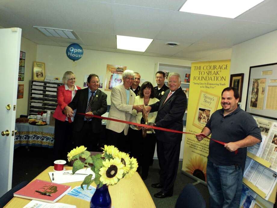 Gathered at the opening of the Courage to Speak Foundation  Family Resource Center on Friday are: (from left to right) Kileen Doyle, board member; Gary Curto, board member; Larry Katz, co-founder; Ginger Katz, founder of The Courage to Speak Foundation; Norwalk Mayor Richard Moccia; Luis Solis, board member and owner of Norwalk Pizza and Pasta, Back Row: Norwalk Poli ceChief Thomas Kulhawik, and David Wrinn, Deputy Chief. Photo: Contributed Photo