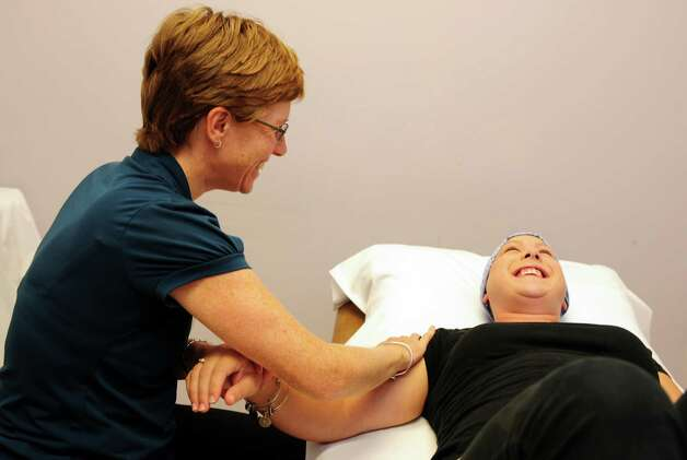 Heidi Taylor, of Trumbull, works with therapist Vikki Winks Tuesday, Sept. 18, 2012 at Ahlbin Rehabilitation Center in Stratford.  Taylor is a breast cancer survivor and is undergoing medical treatment at Bridgeport Hospital following surgery.  The therapy helps Taylor manage the effects of cancer treatment. Photo: Autumn Driscoll / Connecticut Post