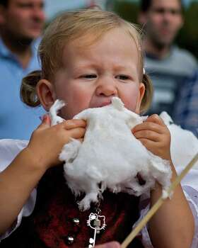 A little girl eats cotton candy, at Oktoberfest. in Munich, southern Germany on Sunday. The world's largest beer festival, to be held through Oct. 7. (AP Photo/dapd, Joerg Koch) Photo: Ap/getty