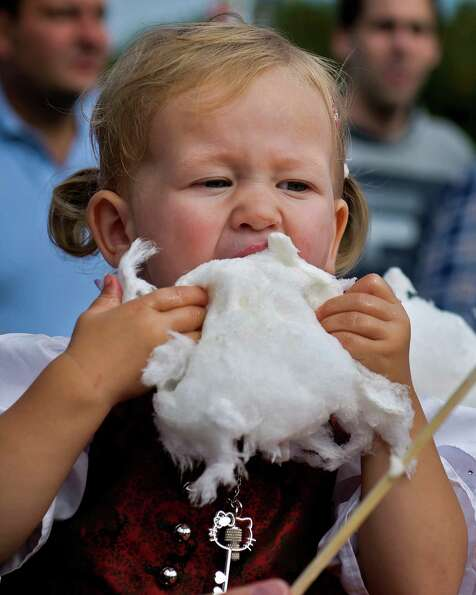 A little girl eats cotton candy, at Oktoberfest. in Munich, southern Germany on Sunday. The world's