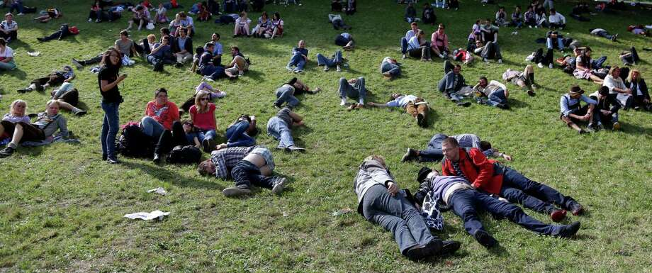 Visitors rest on a meadow at the famous Bavarian Oktoberfest  beer festival in Munich, southern Germany on Sunday. The world's largest beer festival, to be held until Oct. 7.   (AP Photo/Matthias Schrader) Photo: Ap/getty
