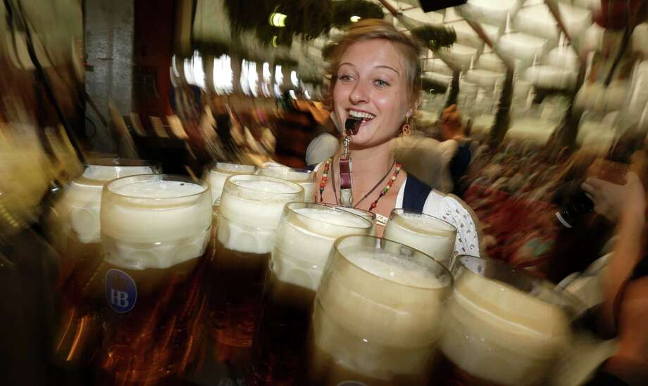 A waitress has her hands full at the Hofbraeuhaus tent after the opening of Oktoberfest in Munich, Germany. (AP Photo/Matthias Schrader) Photo: Ap/getty