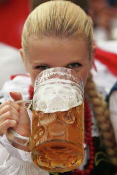 A young Polish woman tips a mug after participating in the opening parade during at Oktoberfest in Munich, Germany. (Photo by Johannes Simon/Getty Images) Photo: Johannes Simon, Ap/getty / 2012 Getty Images
