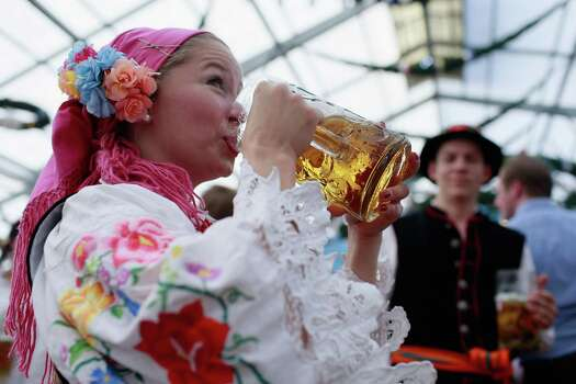 A Polish woman, dressed in traditional Polish clothing, drinks a beer at Oktoberfest.  (Photo by Johannes Simon/Getty Images) Photo: Johannes Simon, Ap/getty / 2012 Getty Images