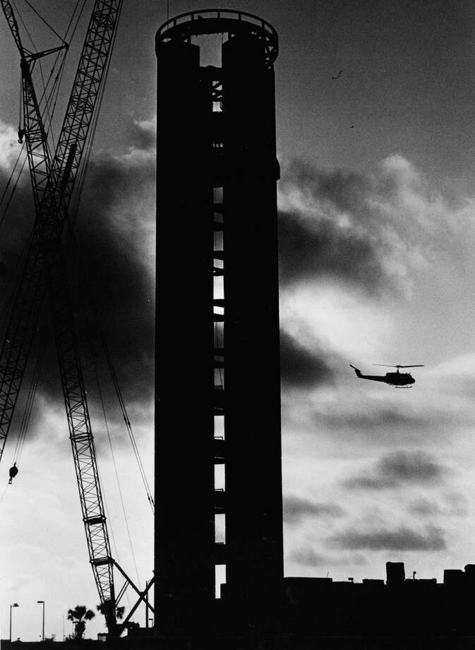 Workmen work on control tower at San Antonio International Airport while an Army helicopter flies past in the early morning. 7-26-1984 Photo: San Antonio Express-News