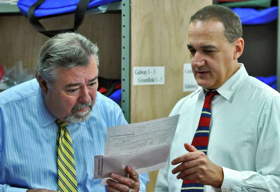 Saratoga County Election Commissioners Roger Schiera, left, and Bill Fruci, right, look over a ballot during a count of absentee ballots for the Republican primary between State Senator Roy McDonald and his challenger Saratoga County Clerk Kathy Marchione, at the Saratoga County Board of Elections on Monday Sept. 24, 2012 in Ballston Spa, NY.    (Philip Kamrass / Times Union) Photo: Philip Kamrass, Albany Times Union / 00019393A
