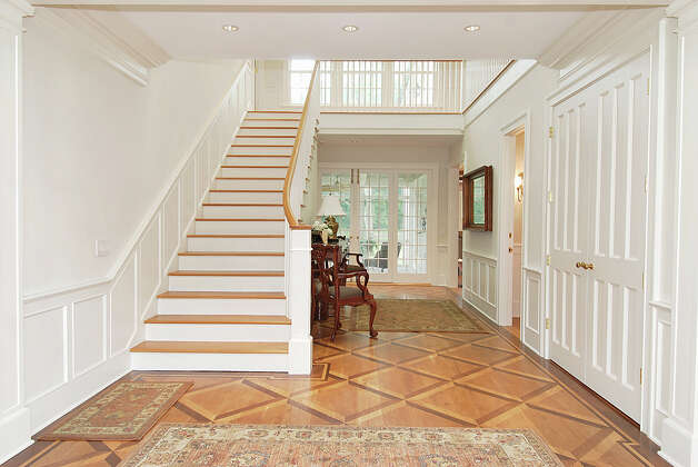 The two-story foyer welcomes visitors into this center hall colonial, the floor of which comprises several types of wood inlaid in a decorative diamond pattern. Photo: Contributed Photo
