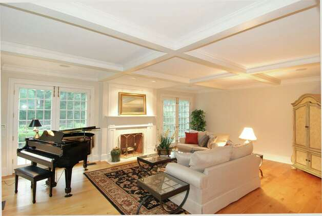The living room boasts a fireplace and, like the two-story foyer, a coffered ceiling. Photo: Contributed Photo