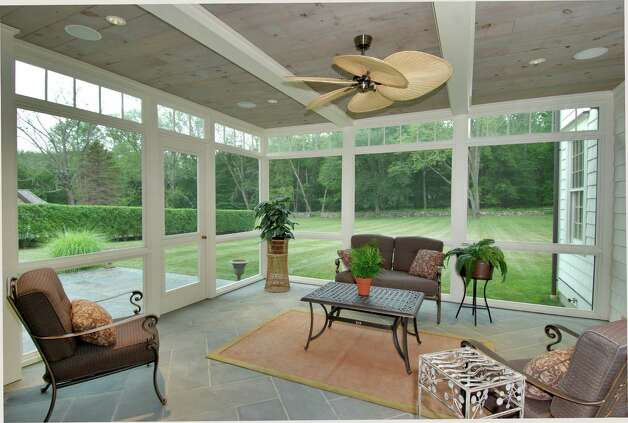 The sunroom on the first floor allows for an unobstructed view of the level yard. Photo: Contributed Photo