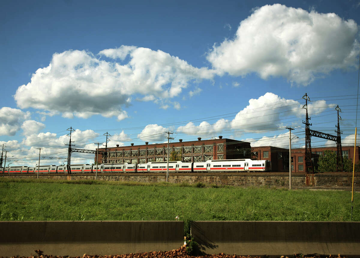 A Metro North train heads past a derelict factory, site of the proposed new train station on Barnum Ave on Bridgeport's East Side on Monday, September 24, 2012.