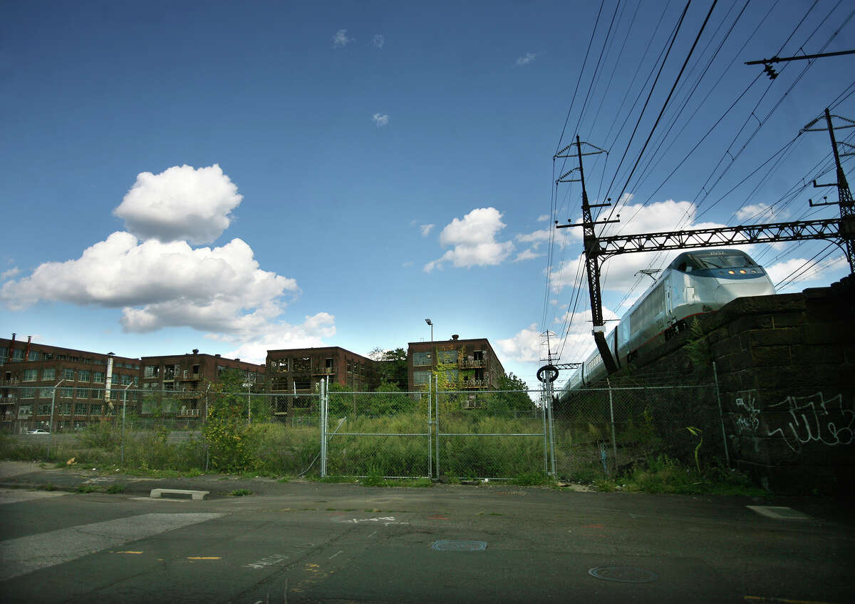 An Acela train heads past a derelict factory, site of the proposed new train station on Barnum Ave on Bridgeport's East Side on Monday, September 24, 2012.