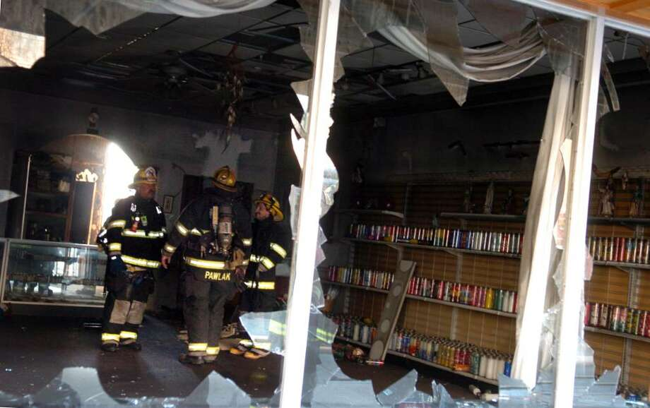 Firefighters survey damage done to Botanica Okalanque, a spiritual shop on Main Street in Ansonia, following a fire in the store Tuesday afternoon. Photo: Autumn Driscoll / Connecticut Post