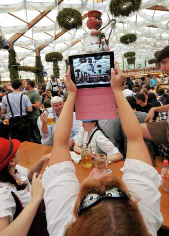 A young woman takes a picture at the Theresienwiese Oktoberfest fair grounds in Munich, Germany, on Monday. Photo: Getty