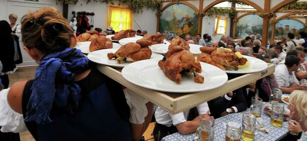 """A woman serves """"Hendl"""" at the Theresienwiese Oktoberfest fair grounds in Munich, Germany on Monday. Photo: Getty"""