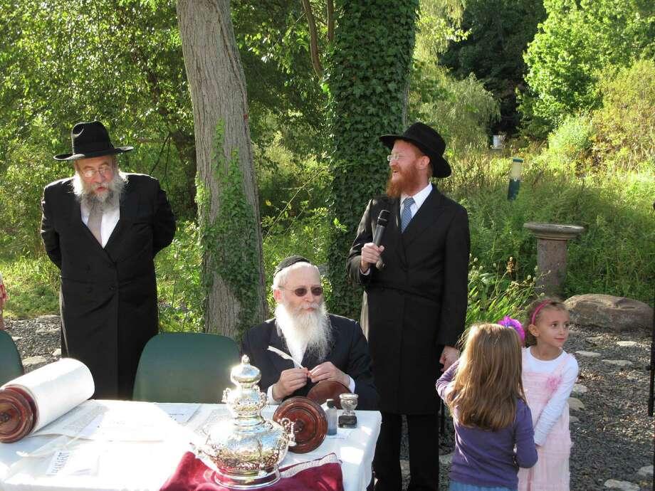 Rabbi Yisrael Deren (left) and Rabbi Levi Mendelow (right) preside over the Torah dedication ceremony Sunday at the Nature Center. 9/23/12. Photo: Tyler Woods