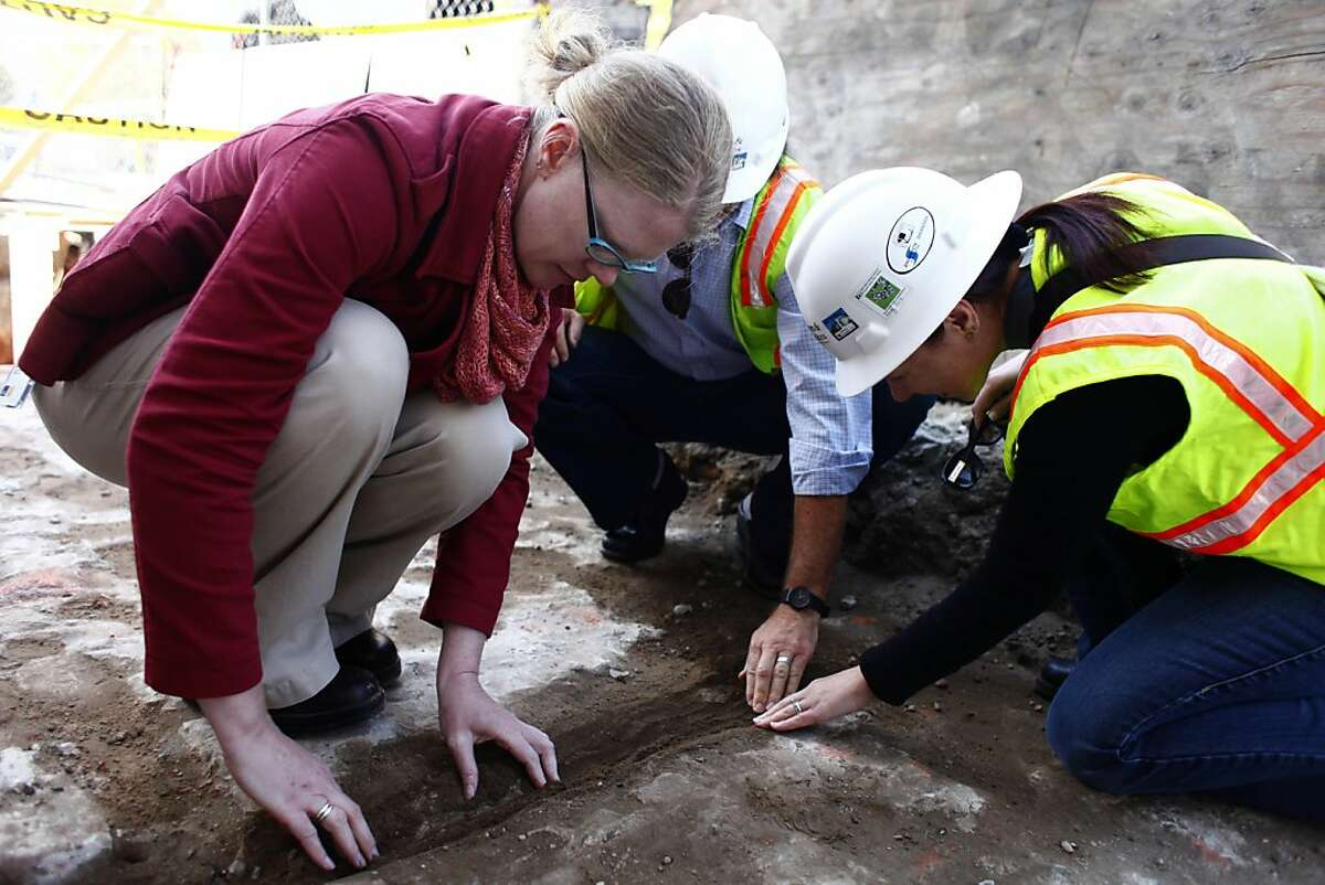 Rebecca Karberg (l to r), U.S. General Services Administration historic preservation specialist and Edward Yarbrough, ICF International senior architectural historian and Joanne Grant, ICF International archaeologist, look closer at a separation in the area believed to the foundation of the original San Francisco City Hall that collapsed during the earthquake and fire of 1906 were discovered during landscaping work at a construction site at 50 U.N. Plaza on Friday, September 21, 2012 in San Francisco, Calif.