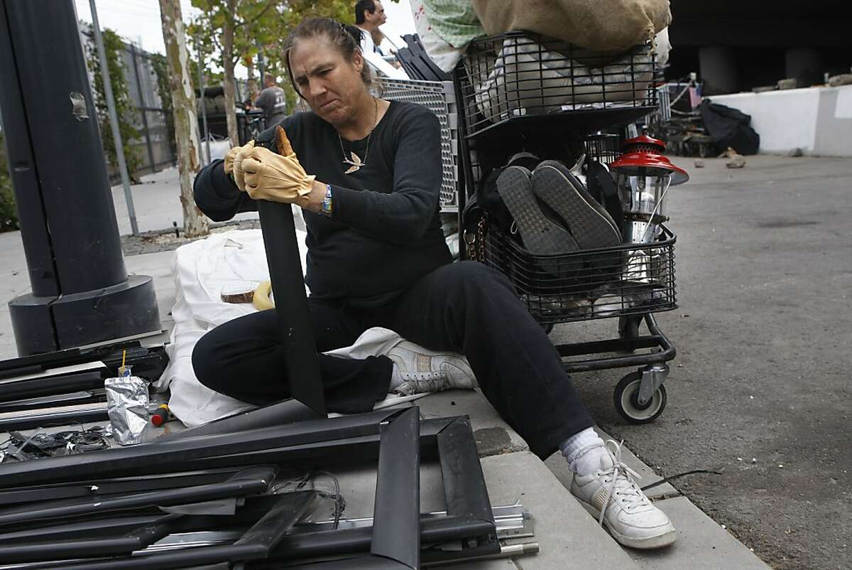 Iona Barger who's been at the homeless encampment under highway 280 on King at Fifth streets in San Francisco, Calif., for six years is removing steel from metal frames she found in a dumpster to sell for food on Monday, September 24, 2012.
