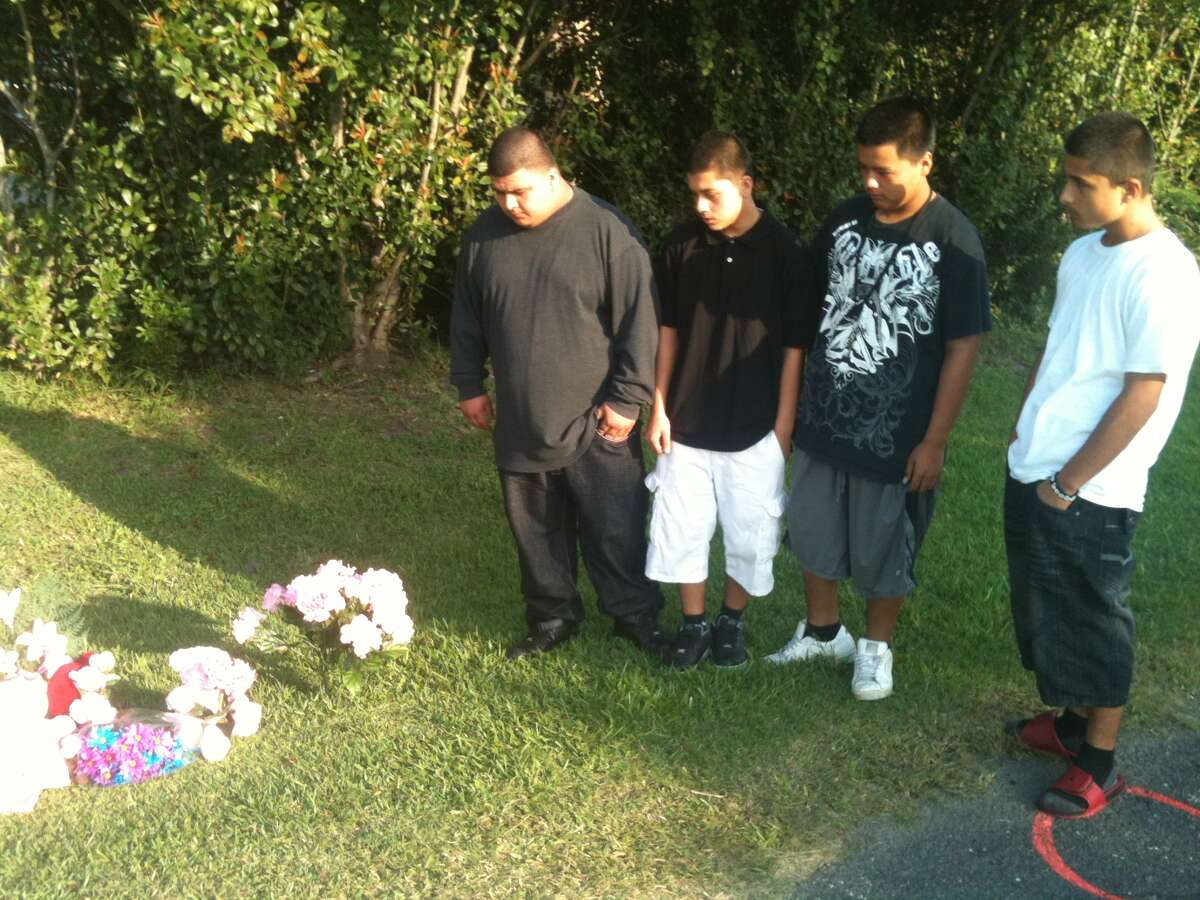 Members of the Lopez family - from left, cousins Jesse, Carlos, Ricardo and Joey - mourn thegirl where she was hit by a truck on Monday. (Robert Stanton/Chronicle)