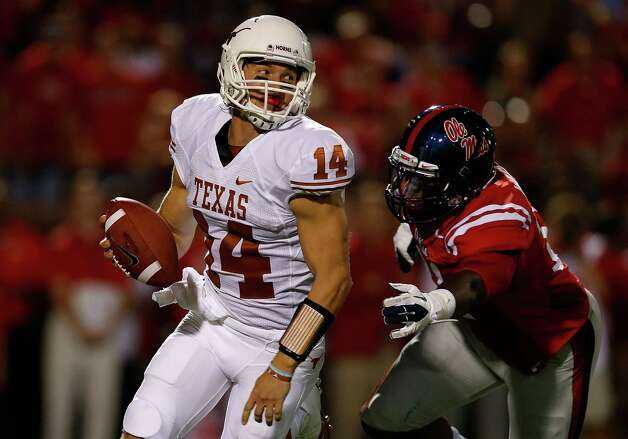 OXFORD, MS - SEPTEMBER 15:  David Ash #14 of the Texas Longhorns fights off the tackle of Channing Ward #11 of the Ole Miss Rebels at Vaught-Hemingway Stadium on September 15, 2012 in Oxford, Mississippi. Photo: Scott Halleran, Getty Images / 2012 Getty Images
