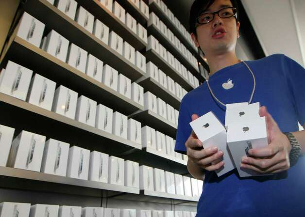 FILE-In this Friday, Sept. 21, 2012, file photo, a staff member of Apple Inc. shows the iPhone 5 to customers at the Apple store in Hong Kong. Apple Inc. said Monday Sept. 24 2012, that it has sold more than 5 million units of the new iPhone 5 in the three days since its launch, less than analysts had expected. (AP Photo/Kin Cheung, File) Photo: Kin Cheung