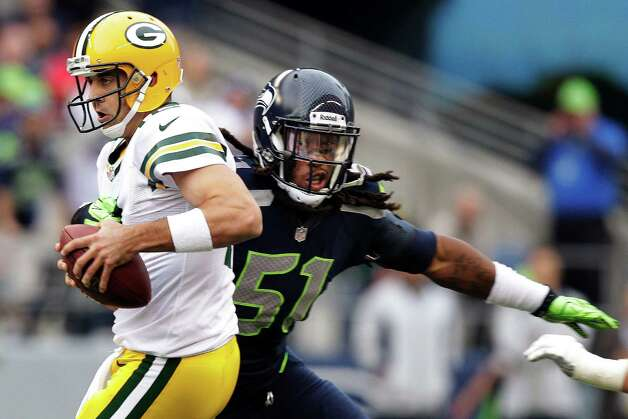 Green Bay Packers quarterback Aaron Rodgers, left, is sacked by Seattle Seahawks defensive end Bruce Irvin (51) in the first half of an NFL football game, Monday, Sept. 24, 2012, in Seattle. Photo: Stephen Brashear, AP / FR159797 AP