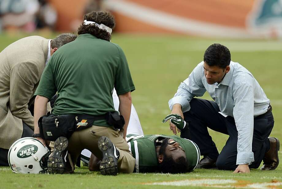 FILE - In this Sunday, Sept. 23, 2012 file photo, New York Jets trainers attend to cornerback Darrelle Revis (24) during the second half of an NFL football game against the Miami Dolphins, in Miami. Revis has a torn anterior cruciate ligament in his left knee that will require surgery, likely meaning he'll miss the rest of the season, the team announced Monday, Sept. 24. (AP Photo/Rhona Wise, File) Photo: Rhona Wise, Associated Press