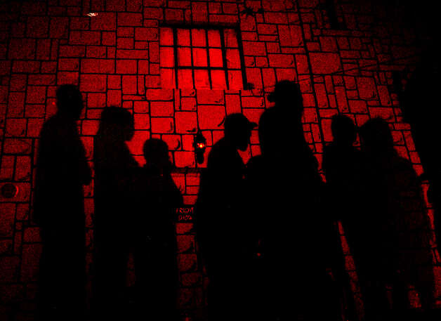 Shadows of people waiting in line to go inside the haunted house Nightmare on Grayson Street Sunday, Nov. 24, 1999, frame the sign Fright Show. The shawdow was cast from the flares warning passing cars of the crowded sidewalks. Photo: ROBIN CORNETT, SPECIAL TO THE EXPRESS-NEWS / SAN ANTONIO EXPRESS-NEWS