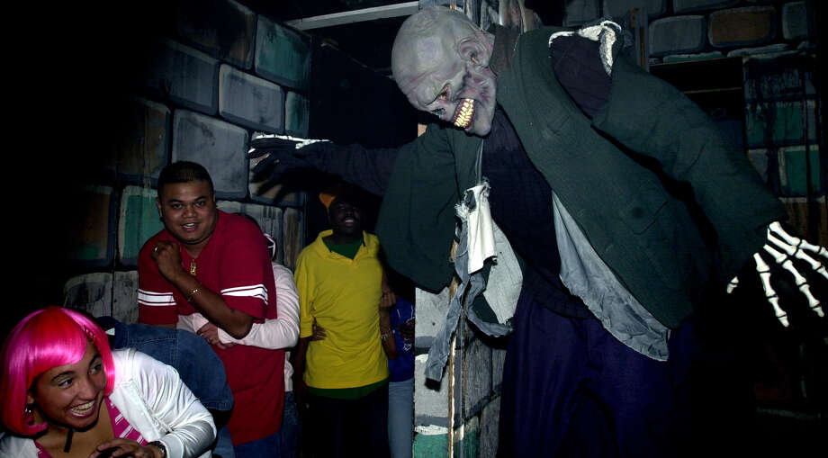 James Escobar (right), as a monster in Frankenstein's lab scares people on Oct. 18, 2003, as they make their way through the Nightmare on Grayson haunted house. Photo: EDWARD A. ORNELAS, SAN ANTONIO EXPRESS-NEWS / SAN ANTONIO EXPRESS-NEWS