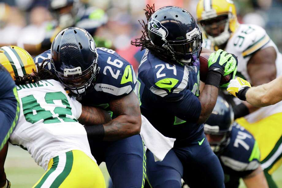Seattle Seahawks running back Marshawn Lynch (24) carries the ball as fullback Michael Robinson (26) blocks Green Bay Packers safety Morgan Burnett (42) in the first half of an NFL football game, Monday, Sept. 24, 2012, in Seattle. Photo: AP