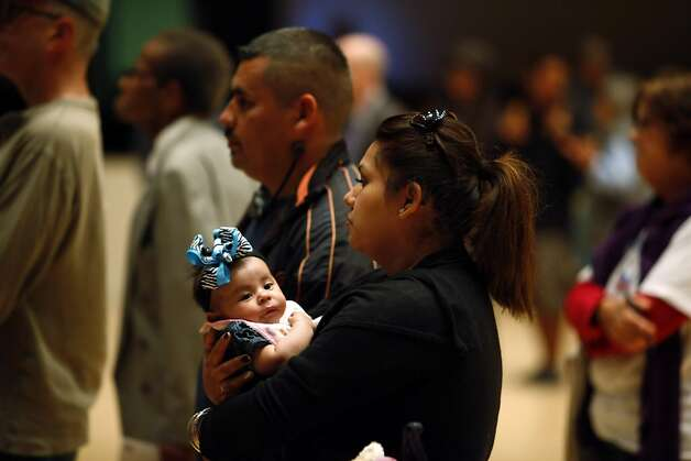 Cynthia Arce holds her daughter Cataleya as she and her husband Jose listen to the panel gathered to give Richmond residents a chance to hear local, state and federal investigatorsâ?? latest findings on the massive Aug. 6 fire at the Chevron refinery at a meeting on Monday, September 24, 2012, in Richmond, Calif. Residents also had a chance to voice their concerns and address specific problems to the panel. Photo: Carlos Avila Gonzalez - San Fran, The Chronicle